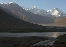 Zonsopgang in het hooggebergte van de riviervallei: in de voorgrond in de schaduw van een stroom van water, wordt de oppervlakte  Royalty-vrije Stock Foto