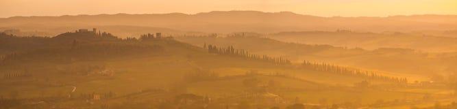 Zonsopgang in het land van Toscanië Warme kleuren op de heuvels en de nevel royalty-vrije stock afbeelding