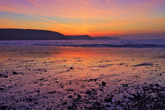 Zonsopgang in het natte zand en de kiezelstenen van het Zoetwaterstrand dat van het Oosten wordt weerspiegeld Royalty-vrije Stock Afbeelding
