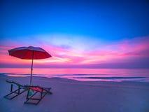 Zonsopgang met dramatische ochtendhemel over overzees met stoel en paraplu op strand royalty-vrije stock fotografie
