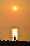 Zonsopgang met een visser en een kleine aak op horizon, Caorle, Italië Royalty-vrije Stock Afbeeldingen