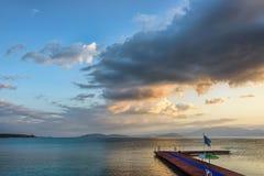 Zonsopgang met pluizige wolken op een gouden blauwe hemel over kalme overzeese wi Stock Foto's