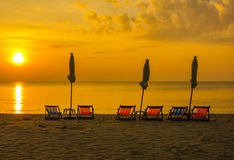 Zonsopgang onder parasol op het strand Stock Foto