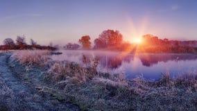 Zonsopgang op de herfst ijzige aard Landschap van heldere dageraad over rivier gras die met rijp op zonlichten glanzen stock foto