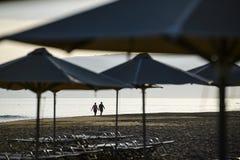 Zonsopgang op de strand lopende mensen stock foto's