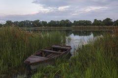 Zonsopgang op een stille rivier Een houten boot bevindt zich op de kust in t royalty-vrije stock afbeeldingen