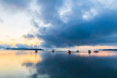 Zonsopgang op het meer met boten, bezinning van zon in water, met mist en wolken op de zomerochtend stock foto