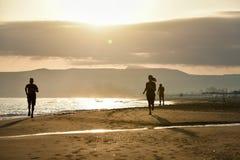 Zonsopgang op het strand met overzees en lopende mensen royalty-vrije stock foto's