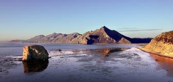 Zonsopgang op Okhotskoe-overzees met mening aan piek` Smeliy ` en roekenkolonie stock foto's