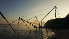 Zonsopgang over Chinese visnetten en boot in Cochin, India stock videobeelden