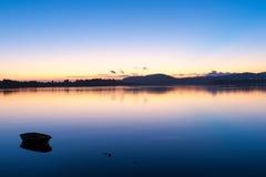 Zonsopgang over de overgangen van de baai blauwe hemel naar roze en sinaasappel van boven de horizon en over kalm water Royalty-vrije Stock Foto's
