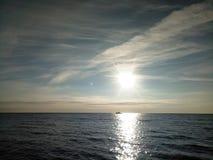 zonsopgang over het kalme overzees Silhouet van een kleine boot op horizon Stock Foto's