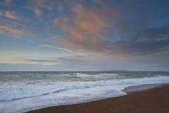 Zonsopgang over oceaan met roze wolken Royalty-vrije Stock Afbeeldingen