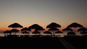 Zonsopgang, strandparaplu's op overzeese achtergrond stock video