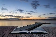 Zonsopgang trillend landschap van pier op kalm meer conceptueel boek Stock Fotografie