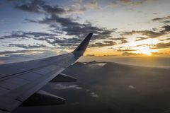 Zonsopgang van een vliegtuig tijdens de vlucht met de erachter mening van zijn vleugel en zon Stock Foto