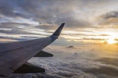 Zonsopgang van een vliegtuig tijdens de vlucht met de erachter mening van zijn vleugel en zon Royalty-vrije Stock Afbeelding