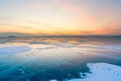 Zonsopganghemel over ijswatermeer met horizonachtergrond royalty-vrije stock fotografie