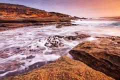 Zonsopganglandschap van oceaan met golvenwolken en rotsen Stock Foto's