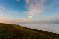 Zonsopganglandschap Vroege die ochtendhellingen met zware mist worden behandeld stock afbeeldingen