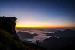 Zonsopgangscène met de piek van berg en cloudscape stock foto