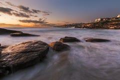 Zonsopgangzeegezicht met rotsen en stromend water bij de lange blootstelling a Royalty-vrije Stock Foto