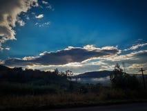 Zonstralen achter wolk stock fotografie
