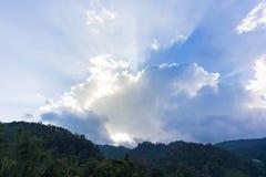 Zonstralen achter wolk in de hemel stock afbeelding