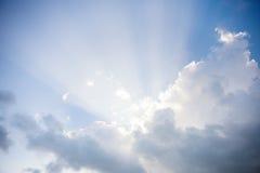 Zonstralen achter wolk in de hemel stock foto's