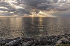 Zonstralen die door wolken over de oceaan glanzen Royalty-vrije Stock Foto's