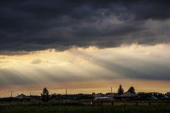 Zonstralen door onweerswolken en wolken Stock Foto