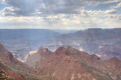 Zonstralen door wolken over Grand Canyon Stock Foto's