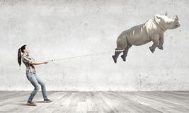 Zoo animal. Young woman holding flying rhino on rope Stock Photo