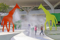 Zoo Miami. Kids having fun  going through the mist which comes out from life size animal sculptures at the entry plaza in Zoo Miami. Florida Stock Photos