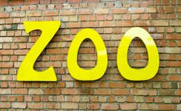 Zoo sign. Yellow zoo writing sign on a brick wall Stock Photography