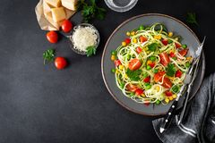 Zoodlie, healthy vegan food - zucchini noodlie with fresh green peas, tomato, bell pepper and corn for lunch. View from above royalty free stock photos