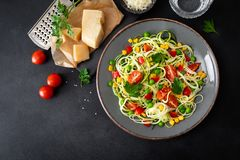 Zoodlie, healthy vegan food - zucchini noodlie with fresh green peas, tomato, bell pepper and corn for lunch. View from above stock images