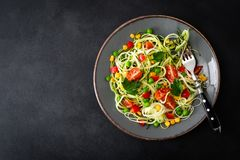Zoodlie, healthy vegan food - zucchini noodlie with fresh green peas, tomato, bell pepper and corn for lunch. View from above royalty free stock images