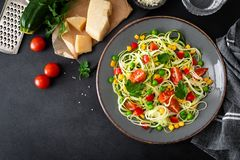Zoodlie, healthy vegan food - zucchini noodlie with fresh green peas, tomato, bell pepper and corn for lunch. View from above stock photography