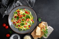 Zoodlie, healthy vegan food - zucchini noodlie with fresh green peas, tomato, bell pepper and corn for lunch. View from above stock photos