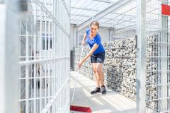 Zookeeper cleaning dog cage in animal shelter. With sweep royalty free stock photos