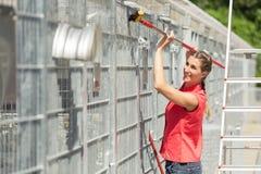 Zookeepervrouw die bij het schoonmaken van kooi in dierlijke schuilplaats werken stock fotografie
