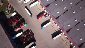 Zoom In Aerial Shot of Industrial Warehouse/ Storage Building/ Loading Area where Many Trucks Are Loading/ Unloading Merchandise. Logistics stock video