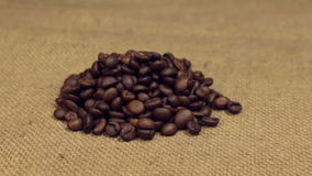 Zoom, approaching is a pile of coffee beans lying on burlap. Close-up. Food stock video footage