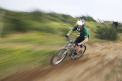 Zoom blur mountain biker. Photo of a mountain bike racer with a zoom-blur effect applied Stock Image