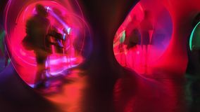 Zoom blur of an people rear view walking into a vivid colorful tunnel. Traveling through time image. Wide aspect ratio of 16:9.  stock photo