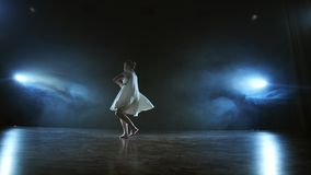 Zoom camera moves around the stage with software and smoke. Girl ballerina dancing in a white dress spinning plastic. While performing pirouettes and rotations stock video footage