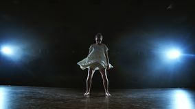 Zoom camera moves around the stage with software and smoke. Girl ballerina dancing in a white dress spinning plastic. While performing pirouettes and rotations stock footage