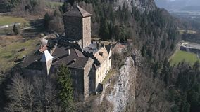 Zoom in castle aerial 4k. Aerial footage of a castle on the cliff in a valley with mountains in the background. Shot in Switzerland in 4k quality stock video footage