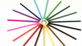 Zoom in on colour pencils in a circle turning against white stock video footage